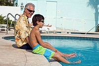 Side profile of a senior man sitting with his grandson at poolside (thumbnail)