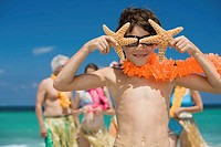 Close-up of a boy holding two starfish in front of his eyes with his grandparents and sister in the background