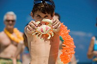 Close-up of a boy holding a crab toy on the beach