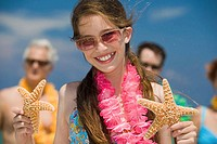 Close-up of a girl holding two starfish with her grandparents and father in the background