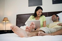 Mature man lying in the bed with a mature woman sitting beside him with a laptop on her lap