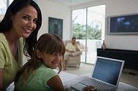 Portrait of a girl using a laptop with her mother sitting behind her