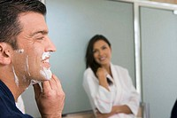 Close-up of a mid adult man shaving and a mid adult woman looking at him