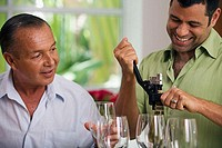Close-up of a mature man unscrewing the cork of a wine bottle with another mature man watching
