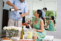 Mature man pouring red wine into a wineglass and a mature woman looking at him