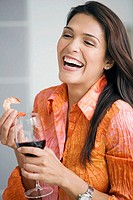 Close-up of a mid adult woman holding a glass of red wine and a shrimp