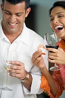 Close-up of a mid adult couple holding glasses of wine and smiling