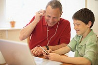 Close-up of a mature man wearing headphones with his grandson sitting beside him