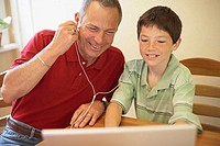 Close-up of a boy and his grandfather wearing headphones and listening to music