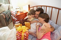 High angle view of a mid adult couple smiling with their daughter in the bed