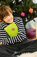 Close-up of a boy holding a Christmas present and smiling