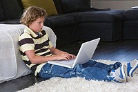 Side profile of a boy sitting on the floor using a laptop