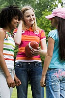 Close-up of three girls talking to each other in a park