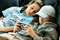 Close-up of a boy playing a handheld video game with another boy lying beside him
