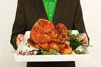 Mid section view of a man holding a roasted turkey on a tray