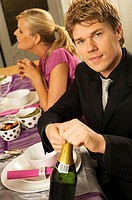 Portrait of a mid adult man opening a champagne bottle with a young woman sitting behind him