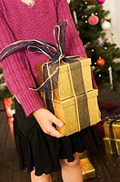 Mid section view of a girl holding two Christmas presents