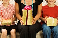 Mid section view of a woman with her son and daughter sitting on a couch holding Christmas presents