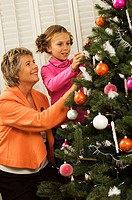 Senior woman with her granddaughter decorating a Christmas tree