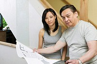 Portrait of a mid adult man holding a blueprint with a young woman beside him