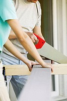 Close-up of a woman standing with a man cutting a plank with a saw
