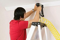 Rear view of a young man using a drill on a wall (thumbnail)