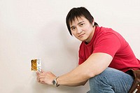Side profile of a young man holding a screw driver and repairing a power outlet (thumbnail)