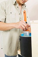 Mid section view of a young man dipping a paintbrush into a paint can (thumbnail)
