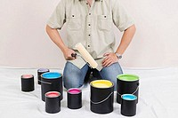 Mid section view of a man holding a paint roller with paint cans in front of him