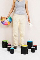 Low section view of a young woman holding color swatches and a paintbrush