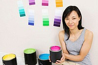 Portrait of a young woman holding a paint can with color swatches on a wall