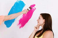 Side profile of a young woman looking at a person's hand painting a wall