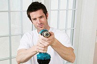 Portrait of a young man holding a drill