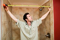 Young man measuring the width of the bathroom with a tape measure