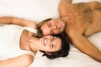 Portrait of a young couple lying in the bed and smiling (thumbnail)