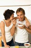 Portrait of a young man eating fruit salad with a young woman looking at him