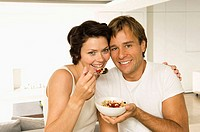 Portrait of a young couple eating fruit salad and smiling