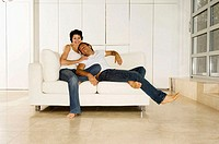 Young man leaning against a young woman sitting on a couch