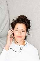 High angle view of a young woman wearing headphones and listening to music