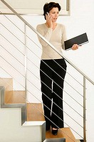 Businesswoman standing on a staircase and talking on a mobile phone