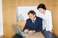 Businessman using a laptop with a businesswoman standing beside him (thumbnail)