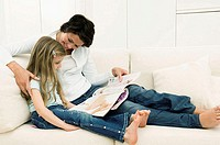 Young woman reading a magazine with her daughter on a couch