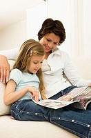 Young woman reading a magazine with her daughter on a couch (thumbnail)