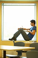 Side profile of a college student sitting on a window ledge and using a laptop