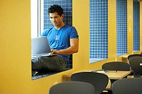 College student sitting on a window ledge and using a laptop