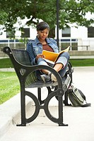 College student sitting on a bench and reading a book