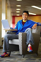 Portrait of a college student sitting in an armchair with a laptop