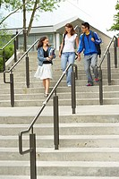 Low angle view of three college students moving down a staircase and smiling