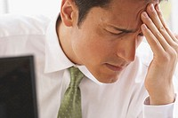 Close-up of a businessman suffering from a headache