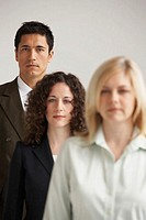 Portrait of two businesswomen and a businessman standing in a row (thumbnail)